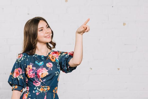 Glimlachende tiener die haar vinger richt op iets tegen achtergrond