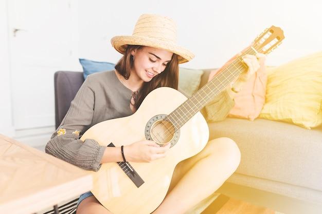 Glimlachende tiener die hoed het spelen gitaar thuis draagt