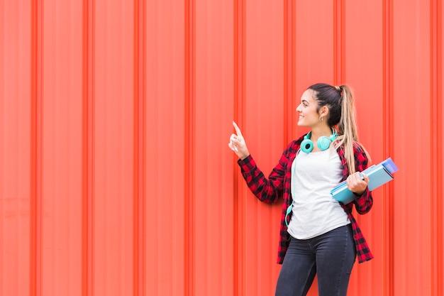 Glimlachende tiener die zich tegen een oranje golfmuur bevindt die haar vinger richt op iets