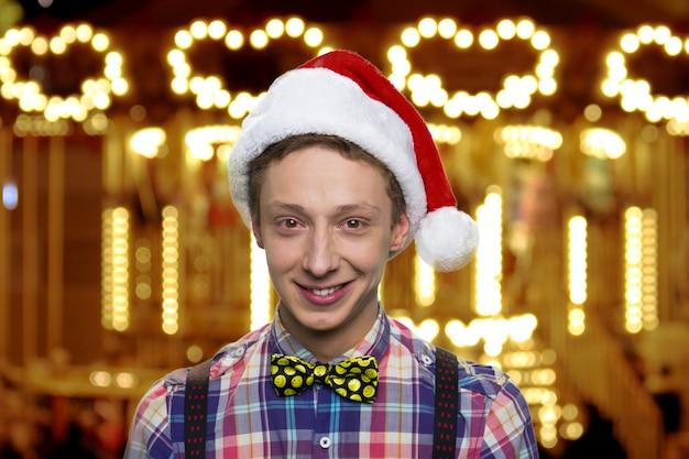 Glimlachende tiener in kerstmuts. vrolijk kerstfeest en een gelukkig nieuwjaar. gloeiende lichten op de achtergrond.