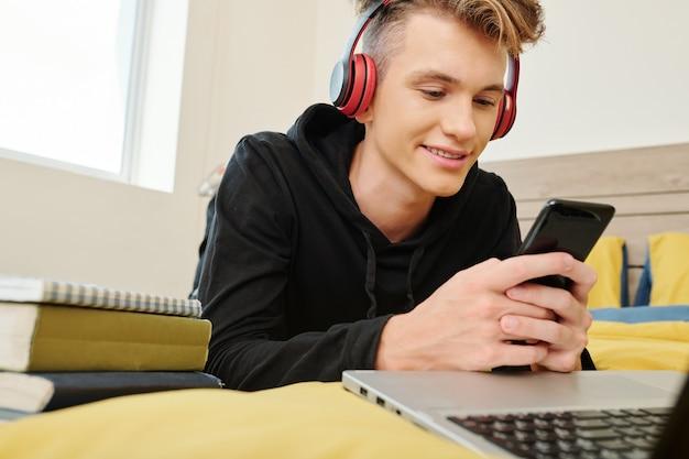 Glimlachende tiener luisteren naar muziek in hoofdtelefoons en spel spelen op smartphone tijdens het rusten in zijn kamer