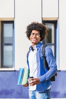 Glimlachende tiener mannelijke studenten dragende rugzak op de stapel van de schouderholding van boek en meeneemkoffiekop die zich bij campus bevinden
