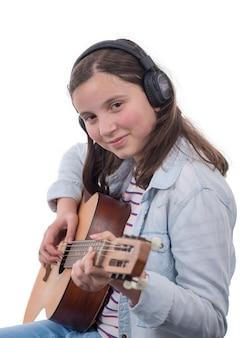 Glimlachende tiener met hoofdtelefoons, die gitaar op wit speelt
