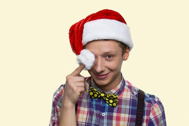 Glimlachende tienerjongen sluit zijn oog met de pompon van de kerstmuts. vrolijk kerstfeest. goed geklede jongen met vlinderdas geïsoleerd op gele achtergrond.