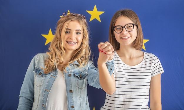 Glimlachende tienermeisjes houden elkaar stevig vast met een eu-vlag achter zich.