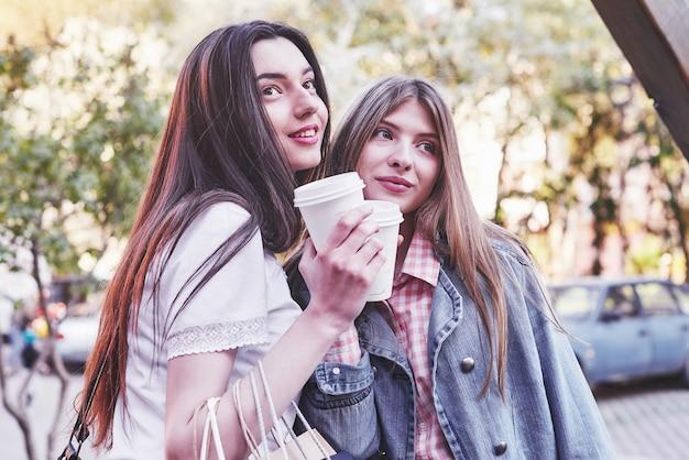Glimlachende tienermeisjes met koffiekopjes op straat. drankjes en vriendschapsconcept.