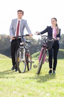 Glimlachende tieners die hun fietsen op een zonnige dag