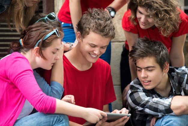 Glimlachende tieners die op internet surfen