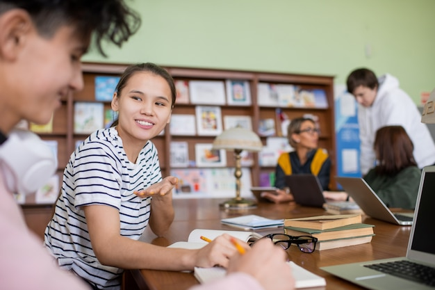 Glimlachende tienerstudent die haar mening over punten van project deelt tijdens het voorbereiden van zijn plan met klasgenoot in bibliotheek