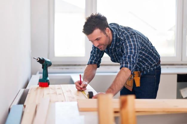 Glimlachende timmerman die houten planken meet