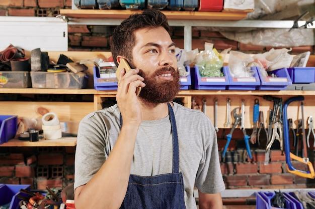 Glimlachende timmerman op planken in zijn atelier