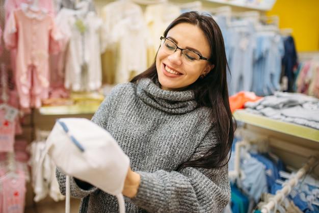 Glimlachende toekomstige moeder kiest babymutsje in de winkel voor pasgeborenen.