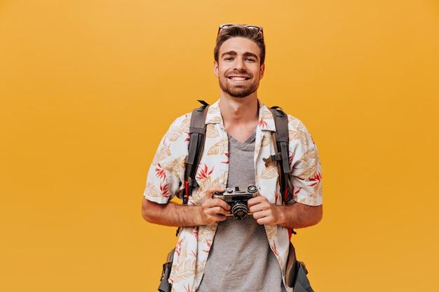 Glimlachende toerist met gemberbaard in zomershirt met korte mouwen en geruit t-shirt met camera en glimlachend op oranje muur