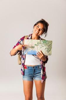 Glimlachende toeristische vrouw wijst op kaart
