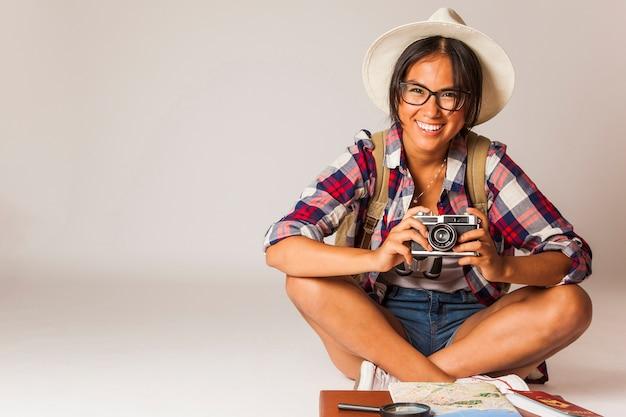 Glimlachende toeristische vrouw zitten met camera