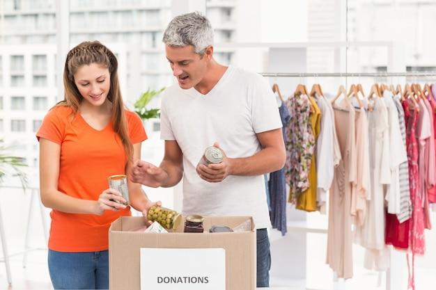 Glimlachende toevallige bedrijfscollega's die schenkingen sorteren