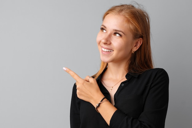 Glimlachende toevallige jonge vrouw die vinger richten op exemplaarruimte