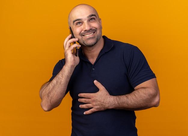 Glimlachende toevallige man van middelbare leeftijd die de hand op de buik houdt en omhoog kijkt terwijl hij aan de telefoon praat, geïsoleerd op een oranje muur
