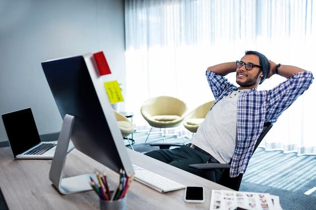 Glimlachende toevallige mens met handen achter hand die bij bureau rusten