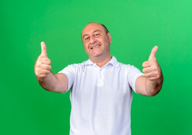 Glimlachende toevallige volwassen mens zijn duimen omhoog geïsoleerd op groene muur