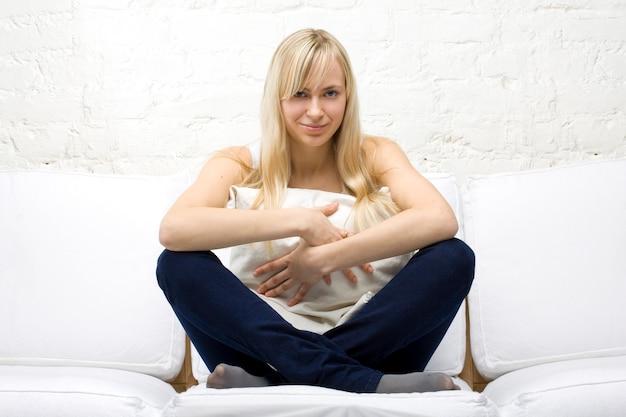 Glimlachende toevallige vrouw die een hoofdkussen op witte laag knuffelt
