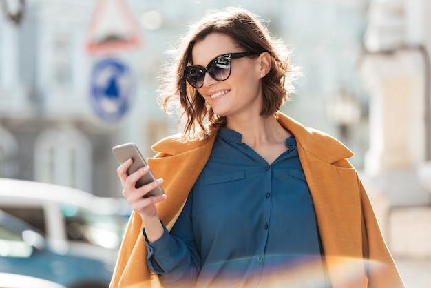 Glimlachende toevallige vrouw die in zonnebril mobiele telefoon bekijkt