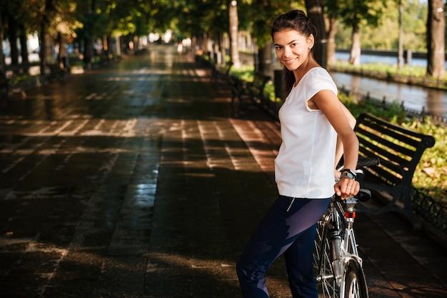 Glimlachende toevallige vrouw met fiets in het straatpark