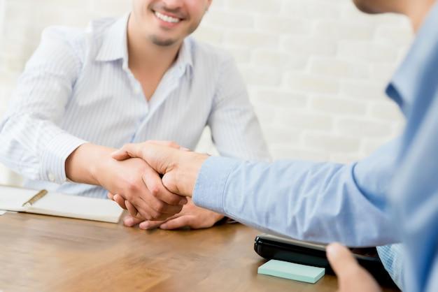 Glimlachende toevallige zakenman die handdruk met zijn partner maken