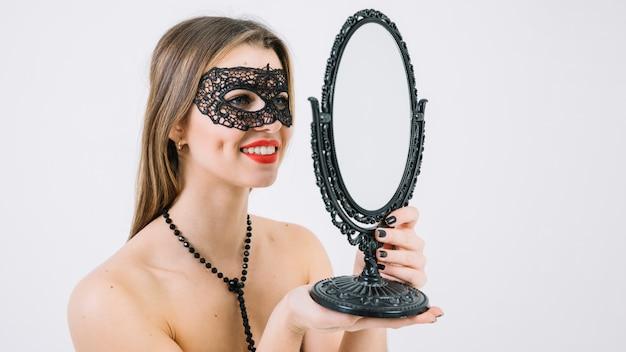Glimlachende topless vrouw die in carnaval masker in hand spiegel kijkt