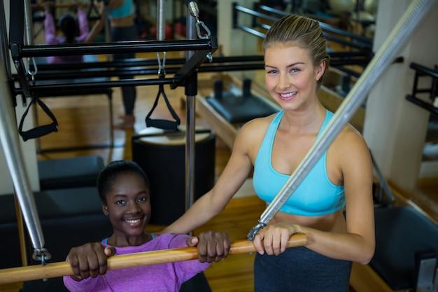 Glimlachende trainer die vrouw met pilates bijstaat op hervormer