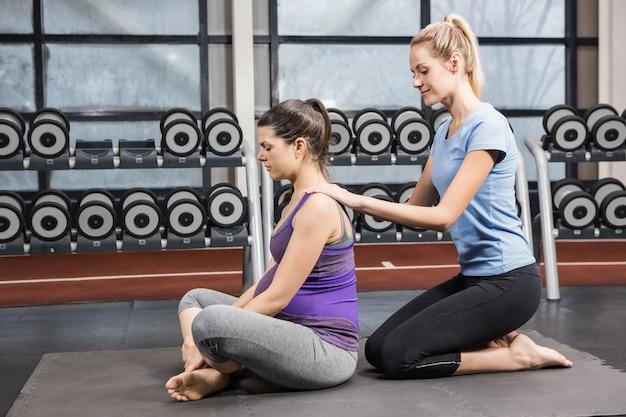 Glimlachende trainer die zwangere vrouw masseren bij de gymnastiek