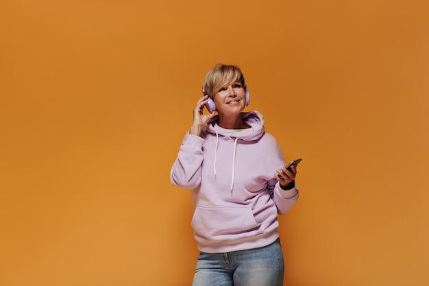 Glimlachende trendy oude dame met blonde cool kapsel in roze sweatshirt en lichte spijkerbroek poseren met lila koptelefoon en smartphones.