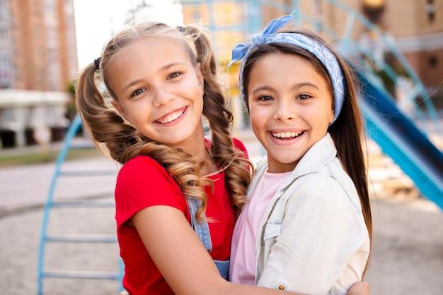 Glimlachende twee meisjes die elkaar koesteren