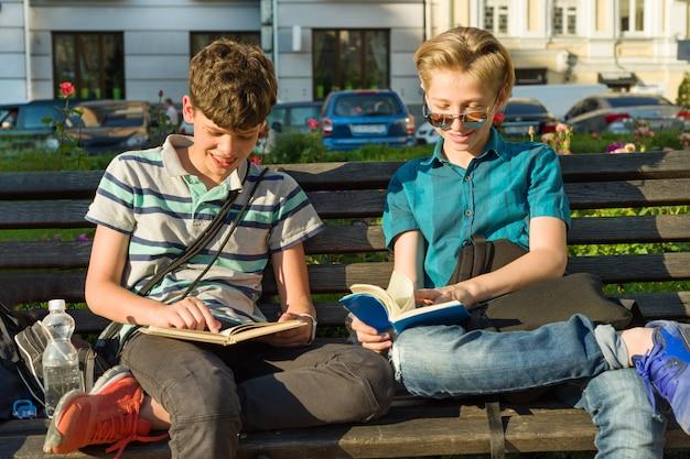 Glimlachende twee schooljongens die boeken lezen