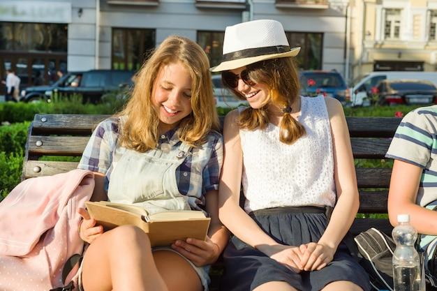 Glimlachende twee schoolmeisjes die boeken lezen die op een bank in de stad zitten
