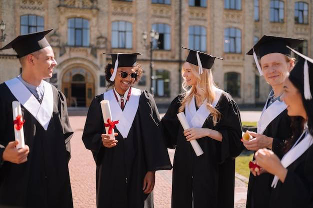 Glimlachende universitair afgestudeerden die op de campus staan en elkaar feliciteren voordat ze vertrekken