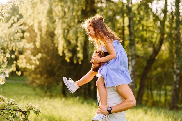 Glimlachende vader die haar dochter op schouders vervoert
