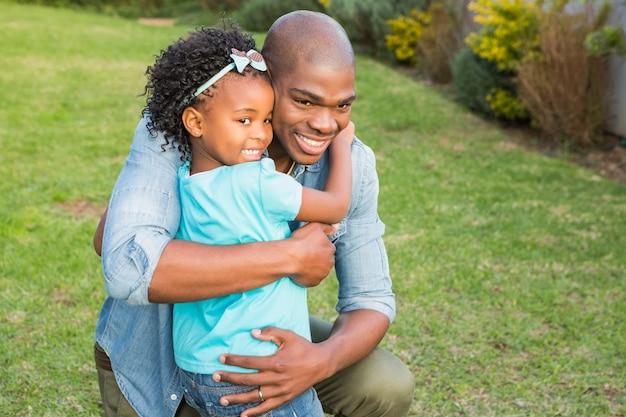 Glimlachende vader die zijn dochter koestert