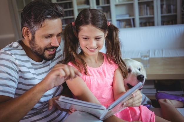 Glimlachende vader en dochter die fotoalbum bekijken in woonkamer