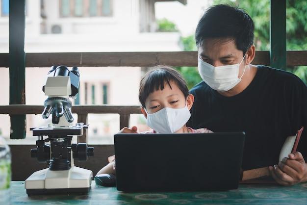 Glimlachende vader en dochter die gezichtsmasker dragen en van huis met laptop en microscoop leren. coronavirus of covid-19 outbreak school sluitingen