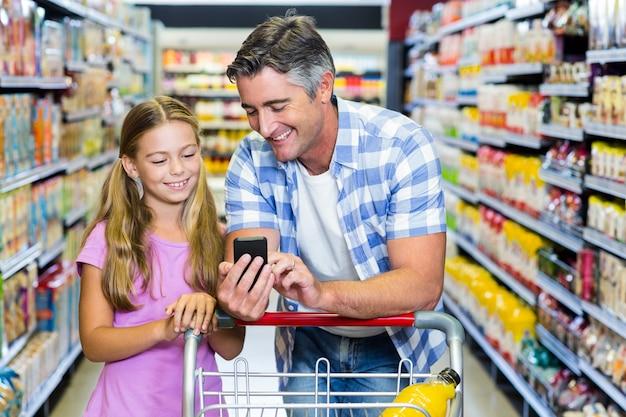 Glimlachende vader en dochter in de supermarkt