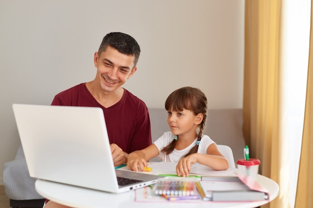 Glimlachende vader en een dochtertje die thuis huiswerk maken, aan tafel in de kamer zitten, met een glimlach naar het laptopscherm kijken, positieve emoties hebben, online onderwijs.