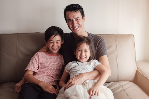 Glimlachende vader en kinderen thuis, gelukkig multicultureel familieportret
