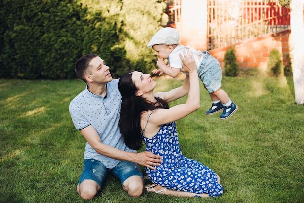 Glimlachende vader en moeder die met hun zoon spelen terwijl ze samen een weekend doorbrengen en op het gazon in de achtertuin van het huis zitten