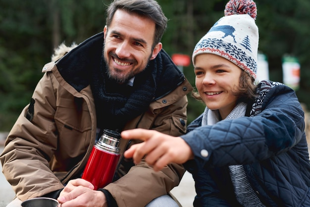 Glimlachende vader en zijn zoon brengen hun boek samen buitenshuis door