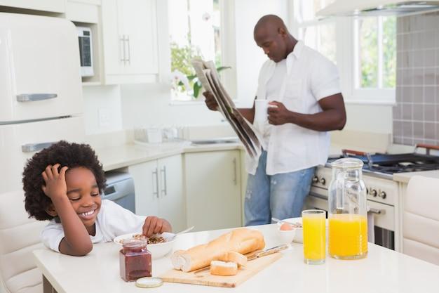 Glimlachende vader en zoon die een ontbijt nemen