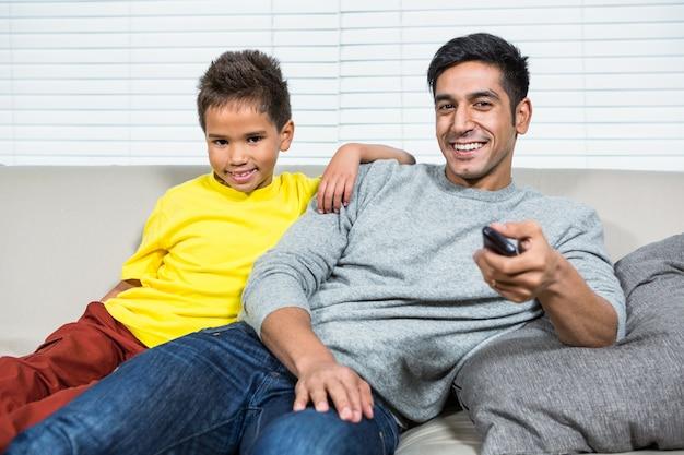 Glimlachende vader en zoon die op tv op de bank letten