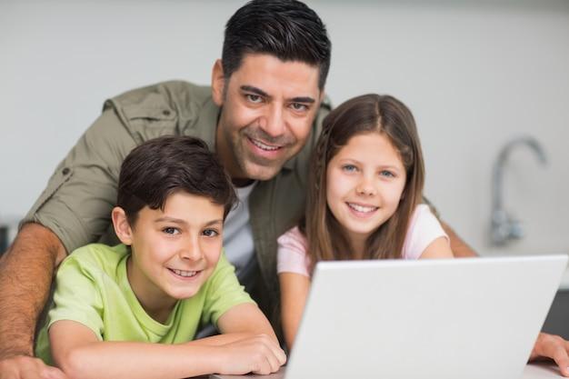 Glimlachende vader met jonge geitjes die laptop in keuken met behulp van