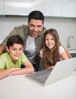 Glimlachende vader met jonge jonge geitjes die laptop in keuken met behulp van