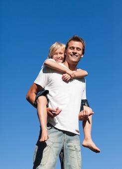 Glimlachende vader met zijn zoon op zijn rug openlucht